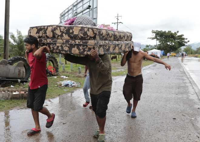 Neighbors help each other as they evacuate the area before Hurricane Iota makes landfall in San Manuel Cortes, Honduras, Monday, Nov. 16, 2020.