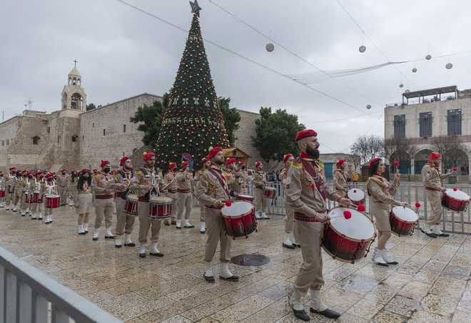 Palestinian scout bands parade through Manger Square at the Church of the Nativity, traditionally recognized by Christians to be the birthplace of Jesus Christ, ahead of the midnight Mass, in the West Bank city of Bethlehem, Thursday, Dec. 24, 2020.